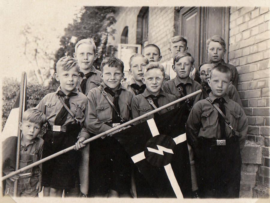 """Zehnjährige in HJ-Uniform gruppiert um einen Wimpel mit """"Sig""""-Rune."""